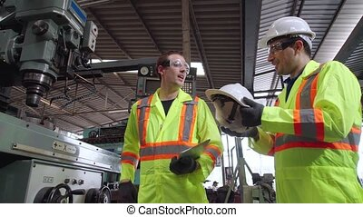 Factory worker warn coworker about safety and give hardhat to him . Injury prevention and safety first concept .