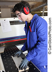 Factory worker wearing ear defenders