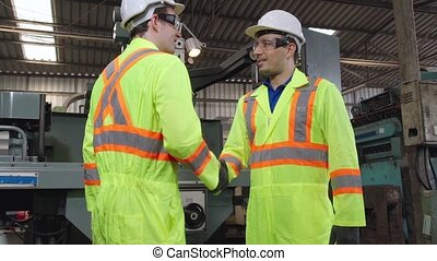 Factory workers handshake with team member in the factory . Industry people teamwork and trust concept .