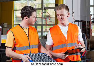 Factory workers in orange protective vest