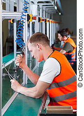Factory workers on the production line using pneumatic screwdriver