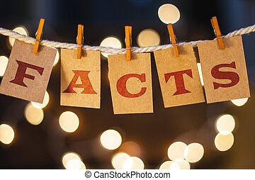 The word FACTS printed on clothespin clipped cards in front of defocused glowing lights.