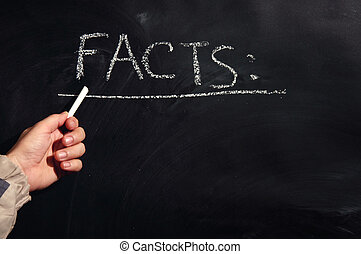 Facts on the blackboard - Male hand is writing FACTS with...