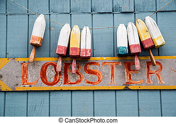Faded Lobster Sign - Buoys hang above a faded sign promoting...
