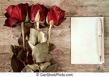 Faded roses and blank paper sheet