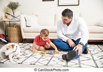 fader, hålla ögonen på, pojke, spelande leksaker, av, hund, hemma