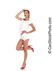 fahion woman in red high heels shorts and shirt posing