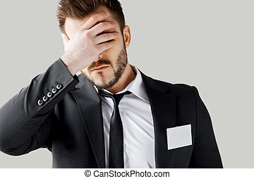 Failed management. Frustrated young man in formalwear covering face with hand while standing against grey background