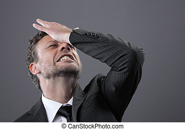 Failure - A stressed out mature businessman holds his head