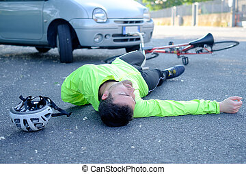 fainted aching man after bicycle accident on the asphalt