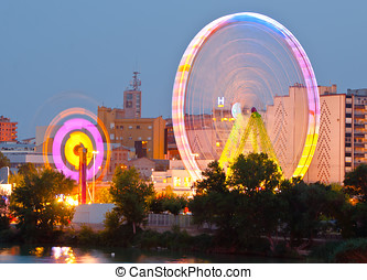 Fair Ferris wheel adorned with lights spinning at dusk