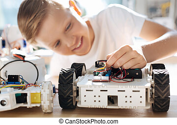 Moment of creation. Adorable upbeat boy sitting at the table and adjusting the wires in his robotic vehicle while looking happy to create