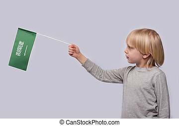 Fair-haired boy holding flag of Saudi Arabia on white background