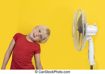 Fair-haired boy with blower relaxing on yellow background. Hot summer
