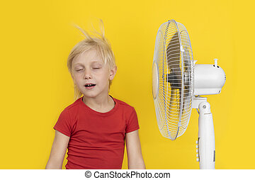 Fair-haired boy with fan relaxing on yellow background. Hot summer.