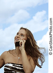 Fair-haired girl over cloudscape with phone