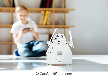 Fair-haired little boy enjoying his new robot toy