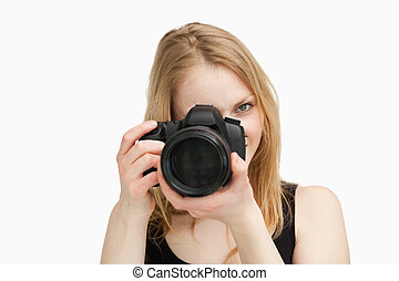 Fair-haired woman aiming with a camera against white ...