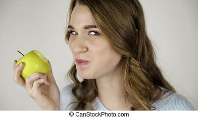 Fair haired woman biting a green apple and licking her lips