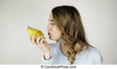 Fair haired woman biting a pear and licking her lips