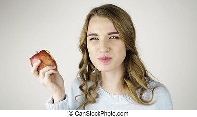 Fair haired woman biting a red apple and flirting