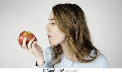 Fair haired woman biting a red apple