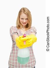 fair-haired woman holding a spray bottle against white ...