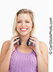 Fair-haired woman holding her headphones against a white ...