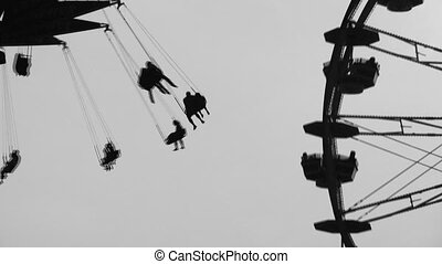 Fairground silhouettes. Two shots. - Swings and ferris wheel...