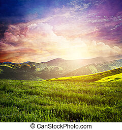 Fairtytale landscape with green grass, mountains, sunset fantastic sky.