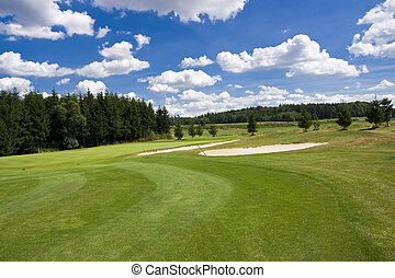 fairway of a beautiful golf course with sand bunkers under dramatic summer sky
