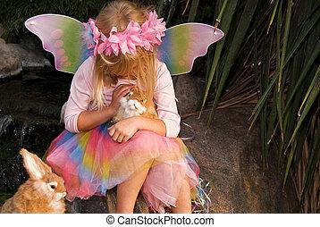 fairy garden - Little girl petting bunny in a garden.