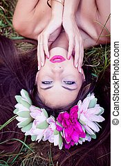 fairy girl: closeup on beautiful young lady having fun lying relaxing on green grass outdoors copy space background