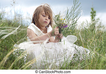 Fairy-tale beautiful little girl on a lawn with the field flowers