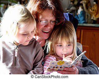 fairy tale hour - aunt with nieces reading in a picture book