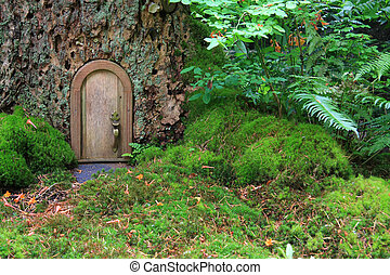 Little wooden fairy tale door in a tree trunk.