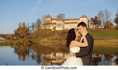 Fairy-tale wedding couple handsome groom swinging beautiful bride at sunset castle background shot in slow motion  close up