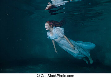 Fairy woman in white dress underwater.
