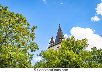 Fairytale castle tower rising up behind green trees