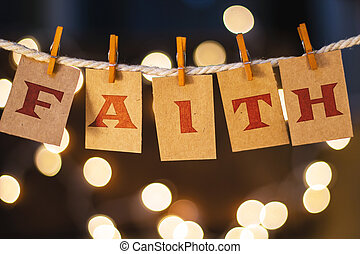 The word FAITH printed on clothespin clipped cards in front of defocused glowing lights.
