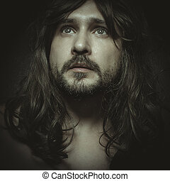 faith concept, man with intense gaze and long hair looking towards the light in prayer pose