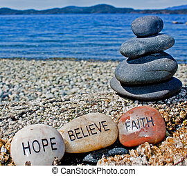 three healing stones written with faith, hope, believe beside a beautiful, ocean side background.