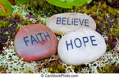 faith hope, believe stones in the forest tree moss.