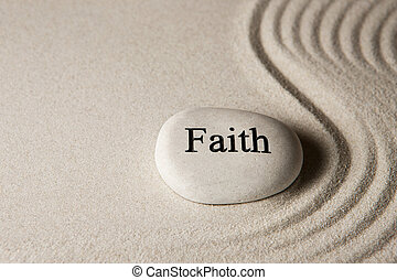 Faith - Inspirational stone surrounded by sand ripples. Zen...