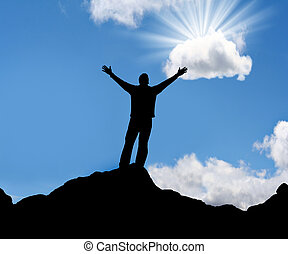 Silhouette of man with arms outstretched to the sun.