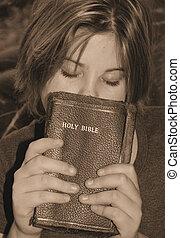faith - a teen girl holding her bible praying