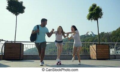 Faithful friends helping a beautiful girl with skateboarding