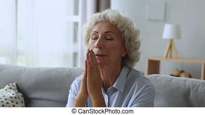 Faithful senior grandmother pray with hope alone at home - ...