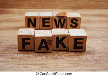 Fake News word alphabet letters on wooden background;