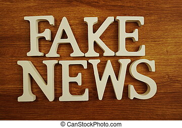 Fake News word alphabet letters on wooden background